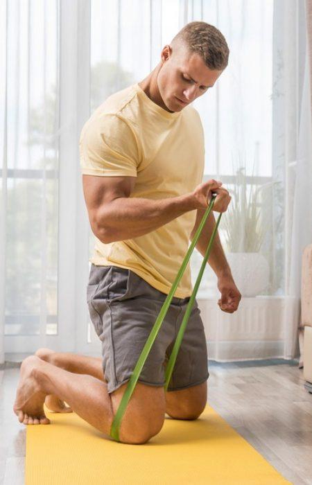 man-doing-fitness-home-using-elastic-band_23-2148700581
